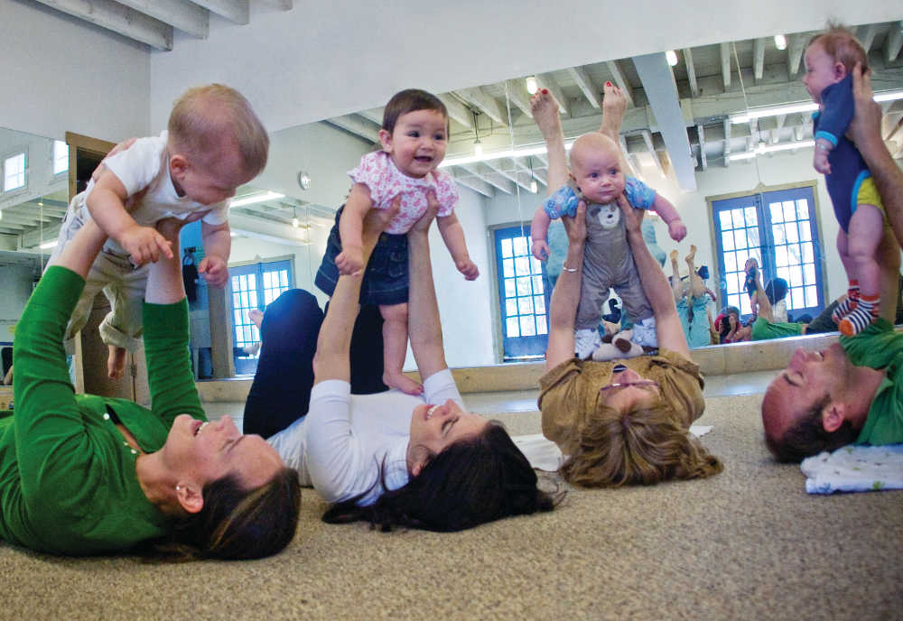 Parents hold their babies in the air in Music Together class.