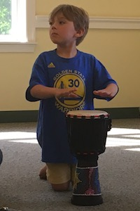 A boy plays a djembe drum in Rhythm Kids class.